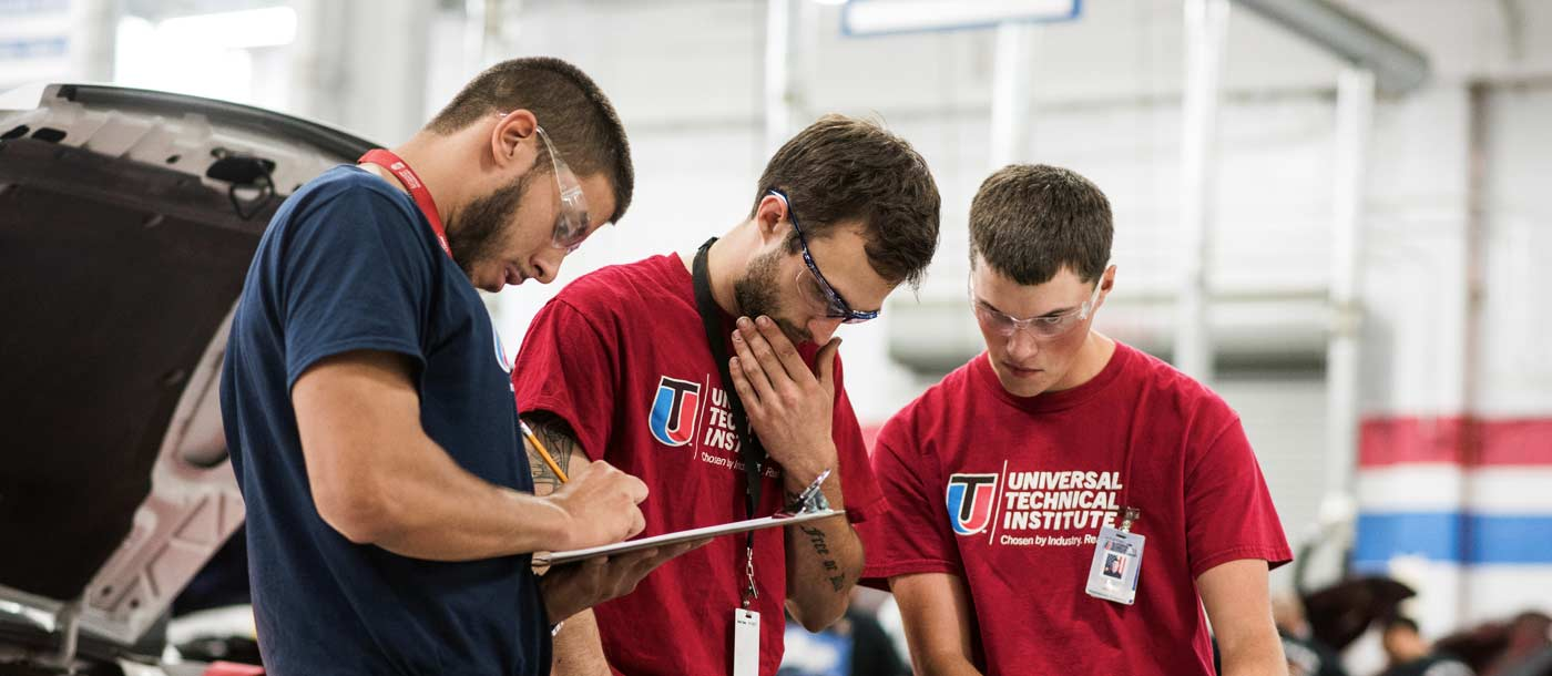 An image of three UTI Houston automotive students in a lab where one is wearing a blue shirt and two are wearing red shirts