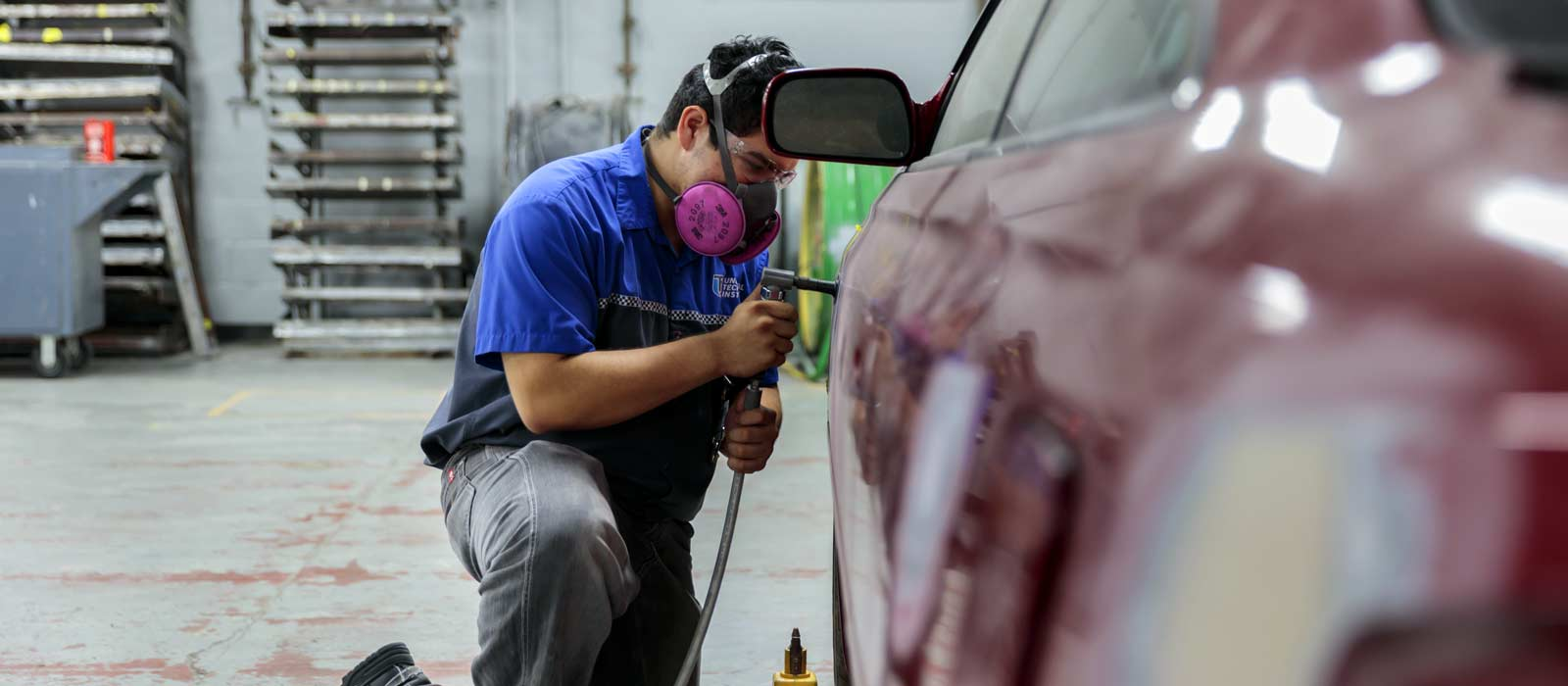 UTI student using one of the 50 and more essential tools for collision repair technicians