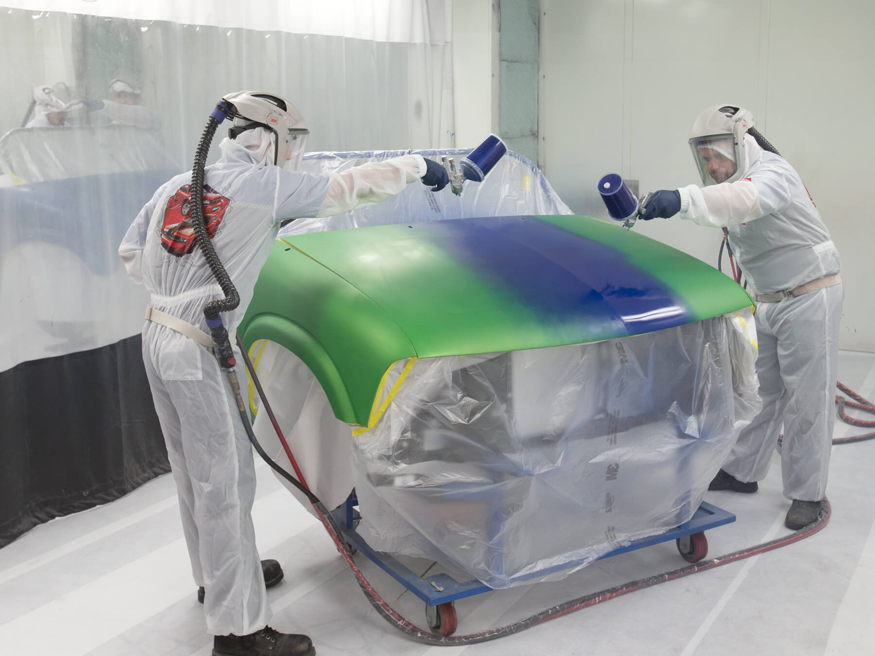 Collision Repair students painting a green car, blue