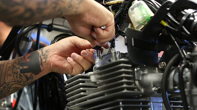 Honda motorcycle student hands-on working in the lab at Motorcycle Mechanics Institute