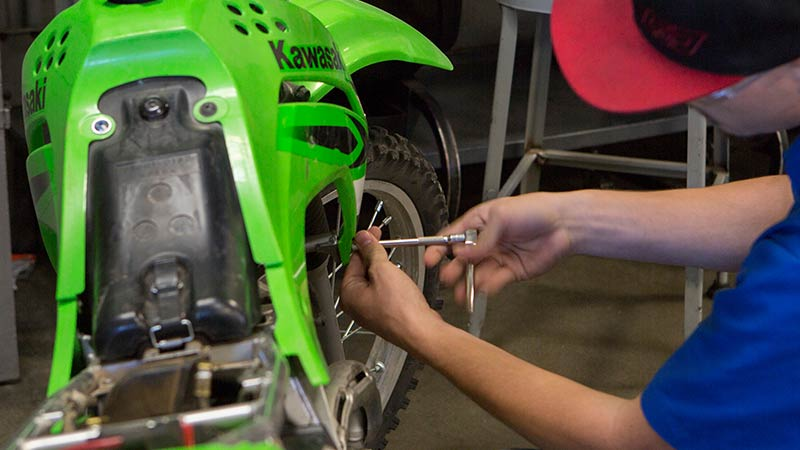 Kawasaki motorcycle student hands-on working in the lab at Motorcycle Mechanics Institute