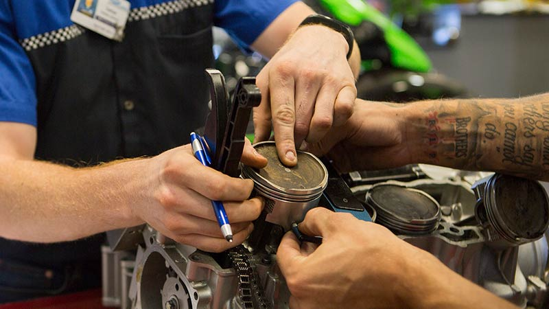Motorcycle Mechanics Institute students working on Kawasaki in the lab