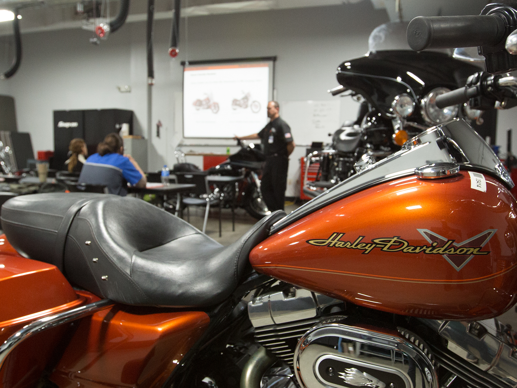 Orange Harley Davidson motorcycle with instructors and students in the background