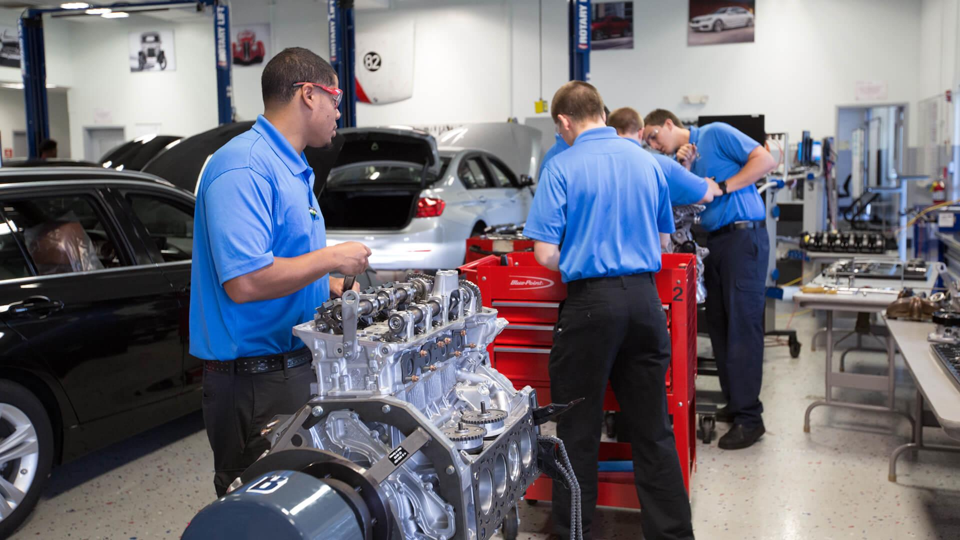UTI students working on an engine in the BMW lab