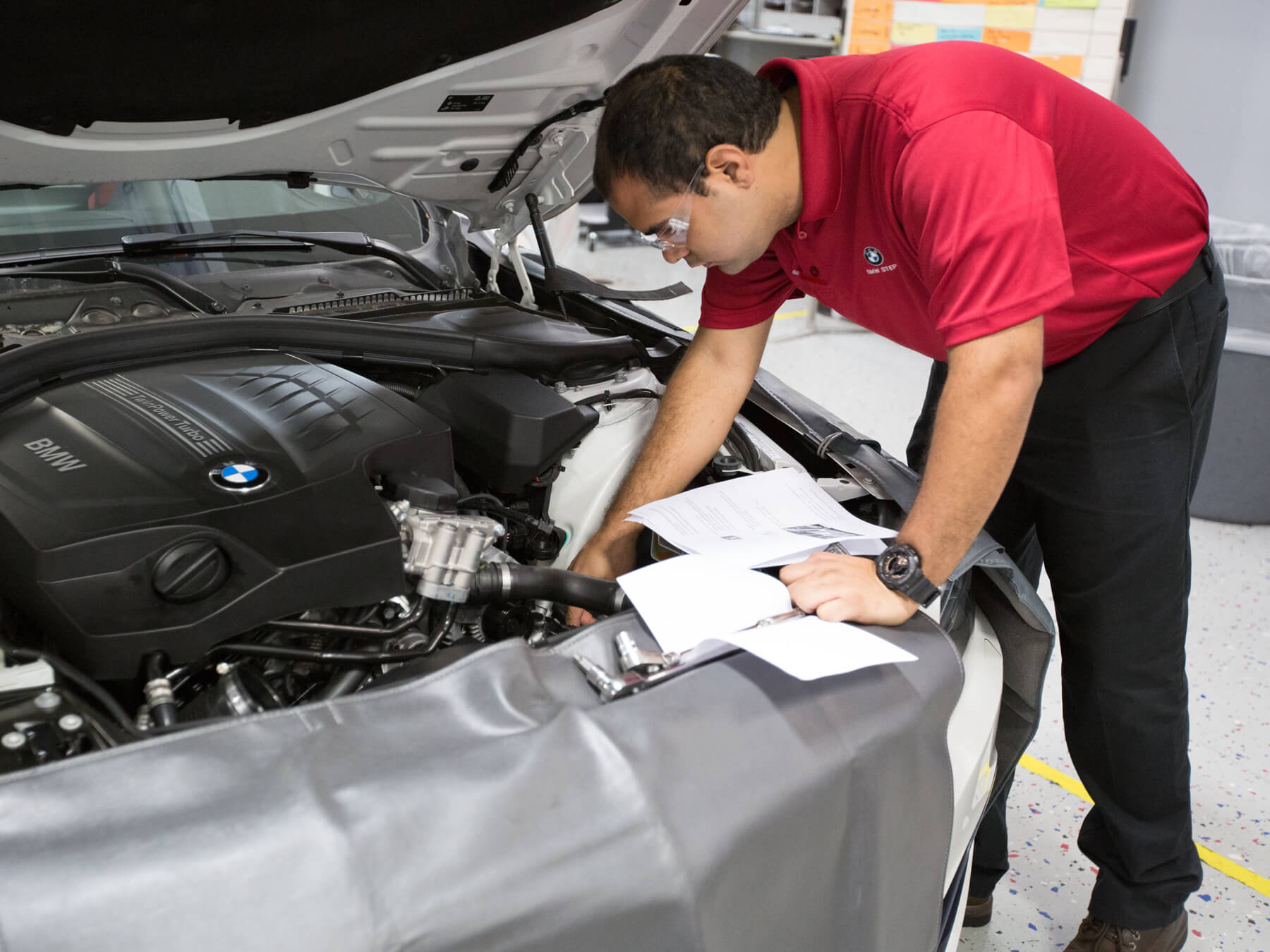 UTI student looking under the hood in the BMW lab