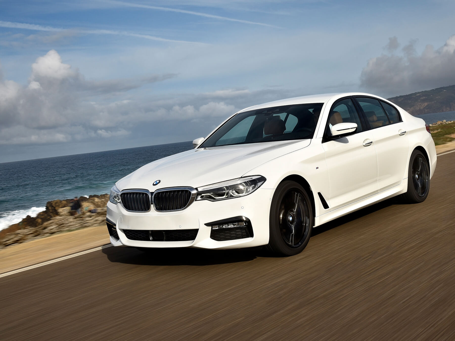 Action shot of a white BMW driving along the oceanside