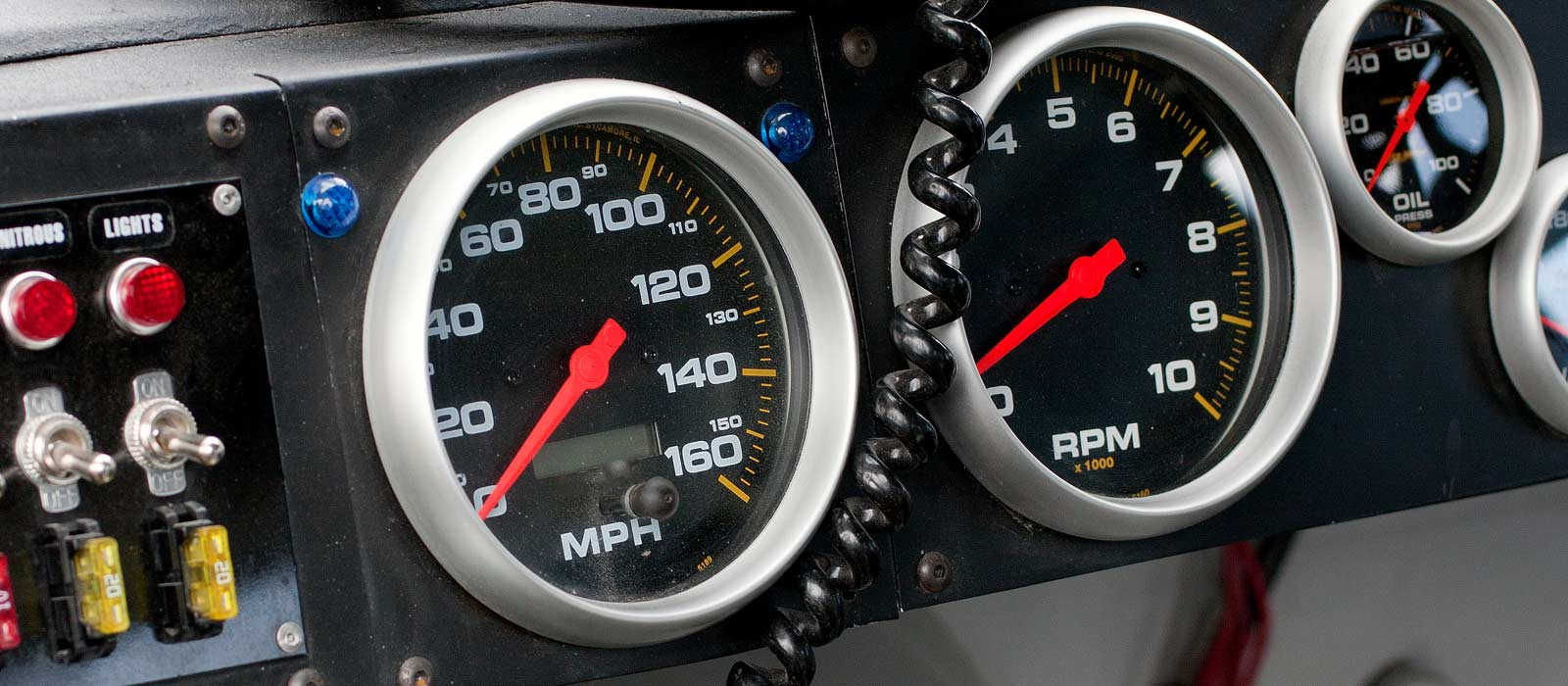 Driver's view of gauges and switches from inside racecar at racetrack near campus