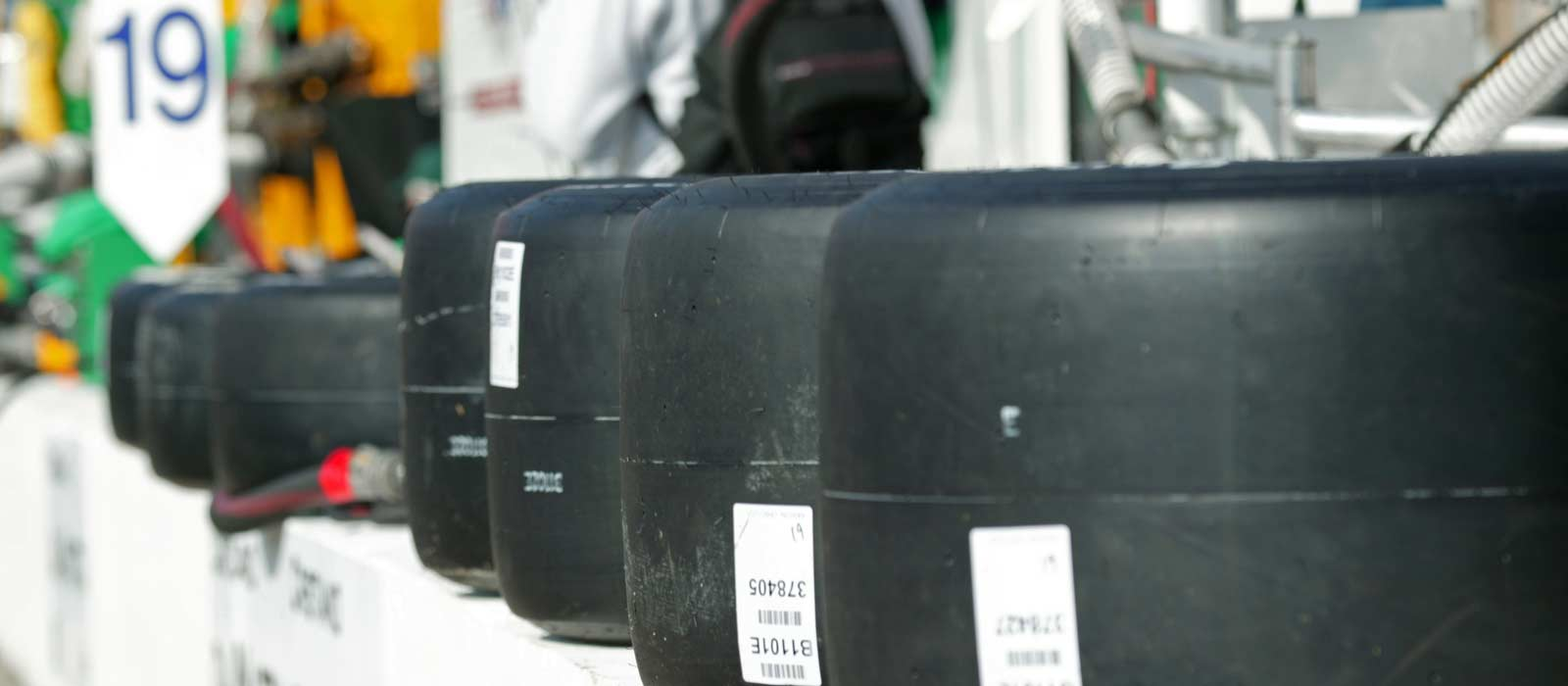 Racecar tires lined up on wall at racetrack near campus