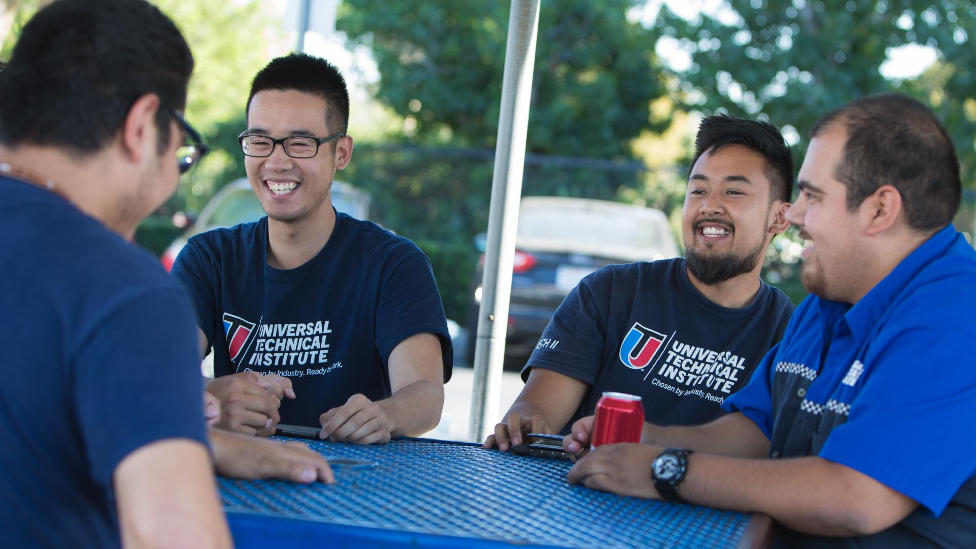 UTI students smiling on break at a blue table