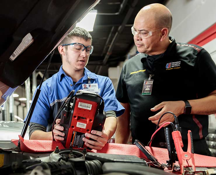 UTI instructor helping student in the lab working with diagnostic tool under the hood 2