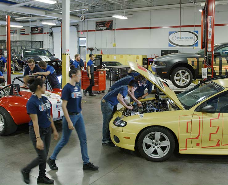 Two female students walking through UTI's lab and several other male students working on cars