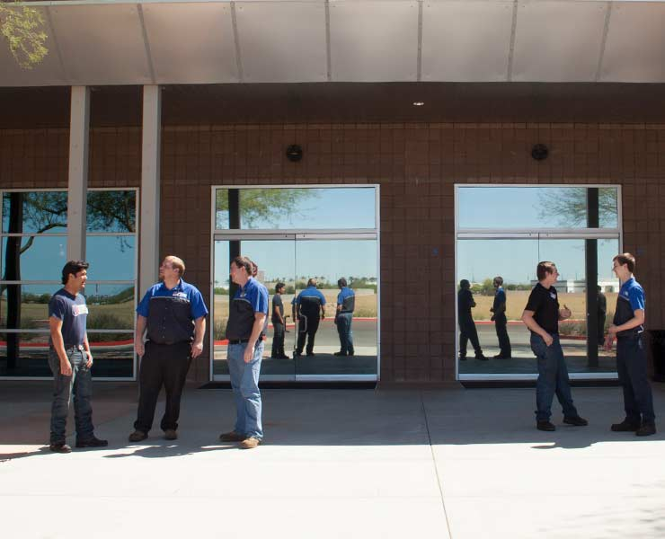 5 male students conversing outside of front entrance of Universal Technical Institute location 2