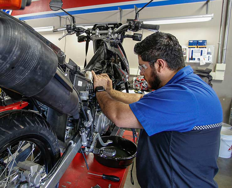 Male student working on motorcycle in Motorcycle Mechanics Institute lab in Orlando, FL