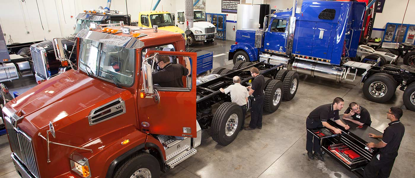 UTI diesel technician students working on a large red diesel truck in the lab