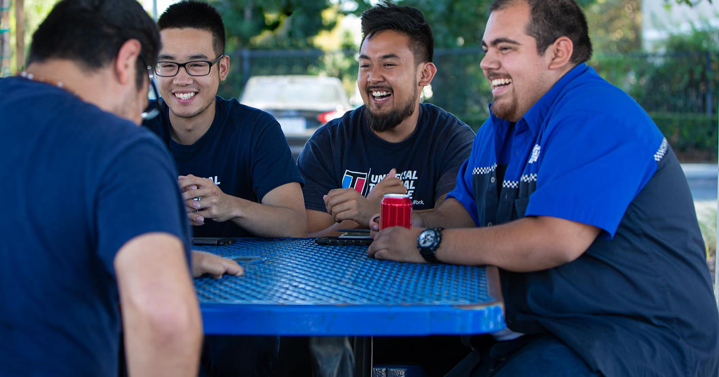 A group of UTI students laughing and enjoying their break in between classes on campus