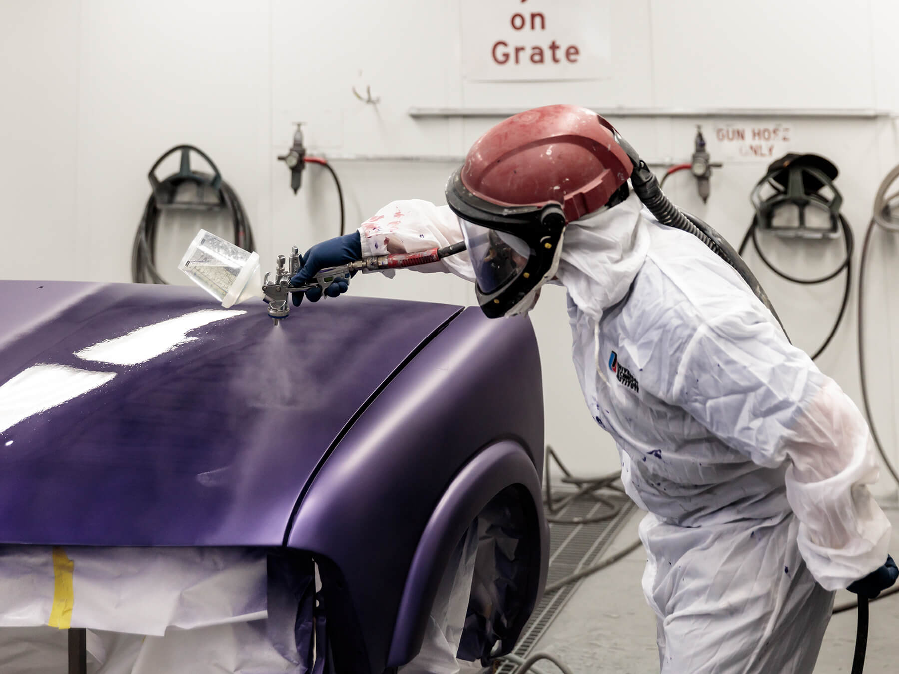 UTI collision student spraying a gloss finish on a purple car