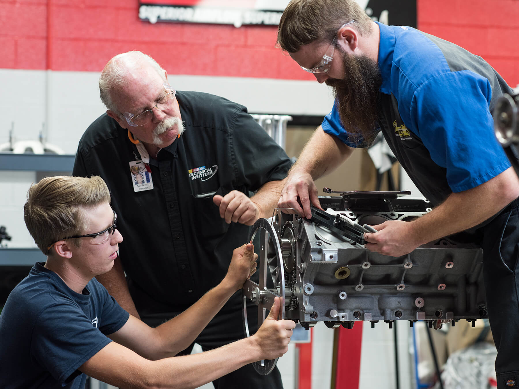 UTI students and instructor working on an engine in the NASCAR Tech lab